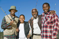 Male members of three generation family holding fishing rods outdoors smiling  portrait