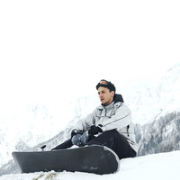 Male snowboarder sitting alone