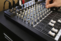 Man adjusting knob on mixing console close-up