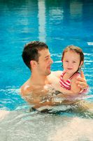 Man and daughter swimming in the pool