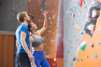 Popular : Man and woman discussing by climbing wall in crossfit gym