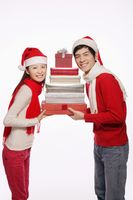 Man and woman holding a stack of gift boxes
