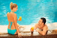 Man and woman relaxing at the edge of pool with glasses of orange juice