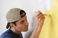 Man carefully painting interior wall close-up