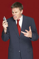 Man in business suit shouting angrily on the hand phone