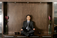 Man in business suit sitting on the shelf meditating