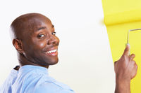 Man painting interior wall yellow portrait