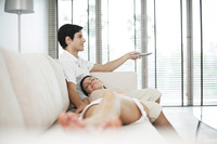 Man watching television with his girlfriend sleeping on his lap