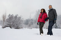 Mature couple walking through snow