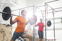 Men lifting barbells in crossfit gym