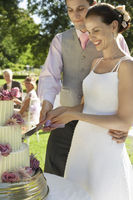 Mid adult bride and groom cutting wedding cake smiling