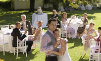 Mid adult bride and groom in garden among wedding guests holding wineglasses embracing