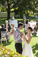 Mid adult bride and groom in garden toasting among wedding guests