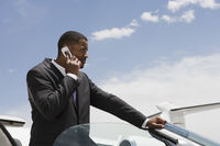 Mid-adult businessman standing in convertible and using mobile phone