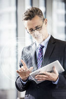 Middle aged businessman using digital tablet in office