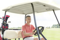 Popular : Middle-aged man driving cart at golf course