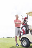 Popular : Middle-aged man standing by cart at golf course