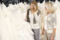 Mother and daughter selecting bridal gown in boutique