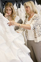 Mother selecting wedding dress for young daughter in bridal store
