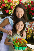 Mother with daughter holding young flowers in plant nursery portrait