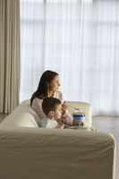 Mother with son eating ice cream in living room