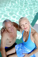 Old couple relaxing by the pool side
