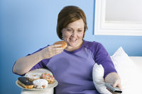 Overweight woman watching television eating