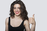 Portrait of a beautiful woman gesturing thumbs up over gray background