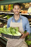 Portrait of a happy young salesperson with bok choy in market