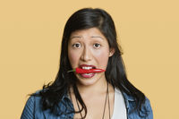 Portrait of a woman with red chili pepper in mouth over colored background