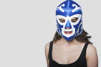 Portrait of a young woman wearing wrestling mask over gray background