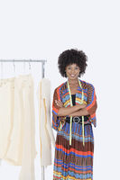 Portrait of an african american female designer with sewing patterns on clothes rack over gray background