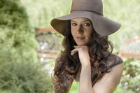 Portrait of beautiful young woman wearing sunhat in park