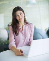 Portrait of confident young businesswoman using laptop at office table