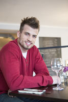 Portrait of happy young man sitting at cafe table