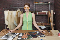 Portrait of pretty female fashion designer standing at table with layouts