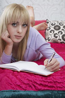 Popular : Portrait of teenager  16-17  lying on bed writing diary