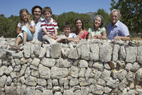 Portrait of three-generation family with three children  6-11  by stone wall