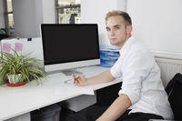 Portrait of young businessman writing notes on paper at desk