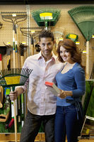 Portrait of young couple with gardening claw in store