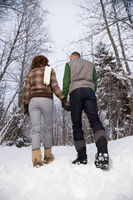 Rear view of a mature couple walking through snow