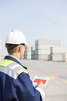 Rear view of middle-aged worker with clipboard in shipping yard