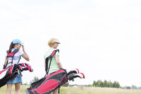 Popular : Rear view of women with golf club bags at course against clear sky