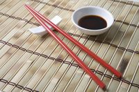 Red chopsticks and side bowl of soy sauce