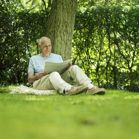 Senior man leaning against a tree reading newspaper