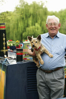 Senior man posing with his dog on the houseboat