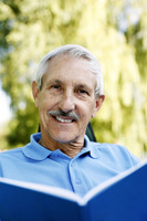 Popular : Senior man smiling at the camera while holding a book