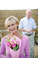 Popular : Senior woman smiling at the camera while holding a bouquet of flowers