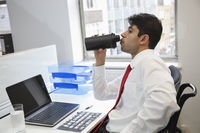 Side view of an indian businessman drinking water at office desk