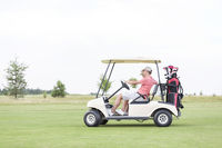 Popular : Side view of couple sitting in golf cart against clear sky